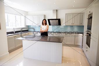Portrait Of Female Realtor In Kitchen Valuing House