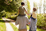 Rear View Of Parents Giving Sons Ride On Shoulders On Walk
