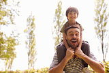 Father Giving Son Ride On Shoulders During Walk
