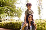 Mother Giving Son Ride On Shoulders During Walk