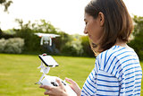 Woman Flying Drone Quadcopter In Garden