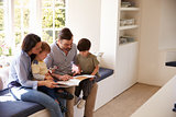 Family Sitting On Window Seat Reading Story At Home Together