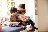 Father And Sons Reading Story At Home Together