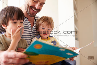 Close Up Of Father And Sons Reading Story At Home Together