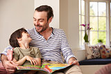 Father And Son Reading Story At Home Together