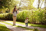 Father And Sons Going For Walk In Summer Countryside