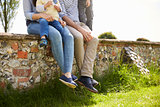 Family Sitting On Wall During Walk In Summer Countryside