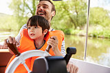 Father And Son Enjoying Day Out In Boat On River Together