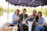 Group Of Friends Enjoying Day Out In Boat On River Together