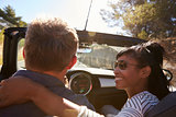 Couple driving, woman looking at man, close up back view
