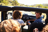 Four friends driving in an open top car, elevated view