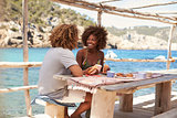 Mixed race couple eating at table by the sea, Ibiza, Spain