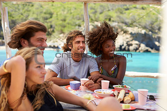 Four friends talking at a table by the sea, Ibiza, Spain