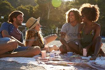 Four friends having a picnic on the beach, lens flare, Ibiza