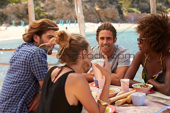 Four friends talking across a table at the seaside, Ibiza