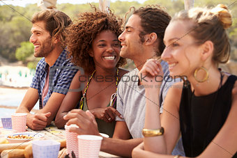 Four friends at a table by the sea, couple kissing, close up