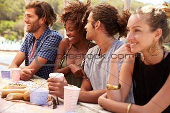Four friends sit in a row at a table by the sea, close up