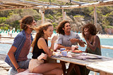 Two couples relaxing at a table by the sea, look to camera