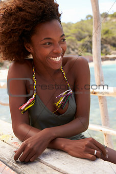 Black woman sitting at a table by the sea, vertical, Ibiza