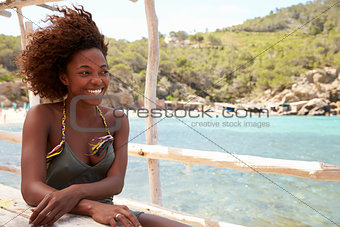 African American woman at a table by the sea, looking away