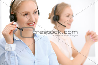 Call center. Focus on beautiful blonde woman in headset