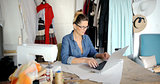 Tailor using laptop in parlour