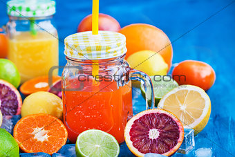Citrus vitamin juice with fresh fruits around