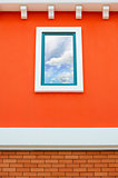 Sky reflection in window glass on orange wall