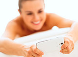Closeup on young woman writing sms while laying on massage table