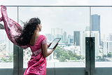 Young Indian woman using a tablet Pc on a terrace in a windy day