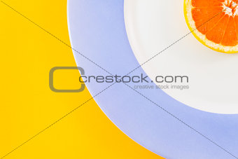 Top view of single grapefruit slice on plate diagonally placed.