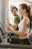 Determined young man smiling while running on treadmill during h