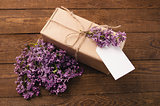 Bouquet of lilacs on a wooden table with a gift box