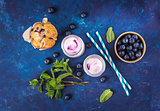 Natural yogurt with fresh blueberries and a muffin.