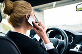 Woman using her phone while driving the car