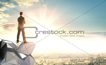 A businessman stands on an abstract construction