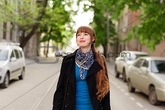 Beautiful young woman walking down the city street on a sunny day, examining the neighborhood.