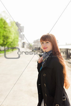 Beautiful red-haired young woman walking down the embankment on a sunny day, examining the neighborhood.