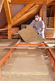 Man places rockwool thermal insulation between wooden scaffoldin