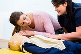 Group of women in first aid class exercising reanimation