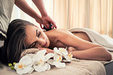 Young woman receiving hot stone massage at spa and wellness cent