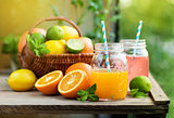 Mix of fresh citrus fruits in basket and juice in glass jars.