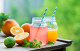 Grapefruit and orange juice in glass jars in the open air.