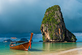 Traditional wooden Thai boat near the shore and high cliff