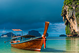 A Thai boat with a long tail near the shore, a blue rain cloud o