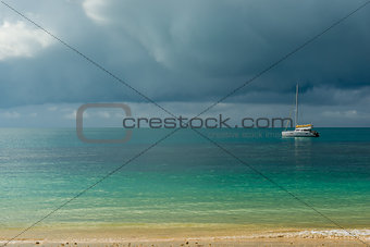 A gloomy sky above the turquoise calm sea and a small white yach