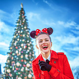 smiling stylish woman near big Christmas tree in Disneyland