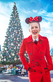 happy stylish woman near big Christmas tree in Disneyland
