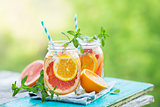Grapefruit and orange water in glass jars in the open air.