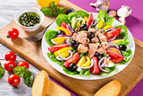 French salad with canned tuna and fresh vegetables and herbs